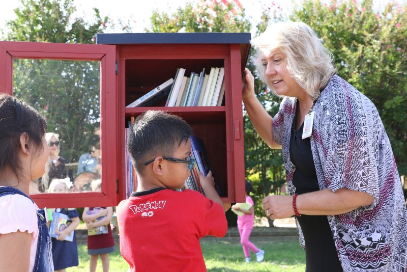 Deanna Tirrell, Media Specialist at Jenks East Elementary, helps students place the first books in the new Little Free Library.