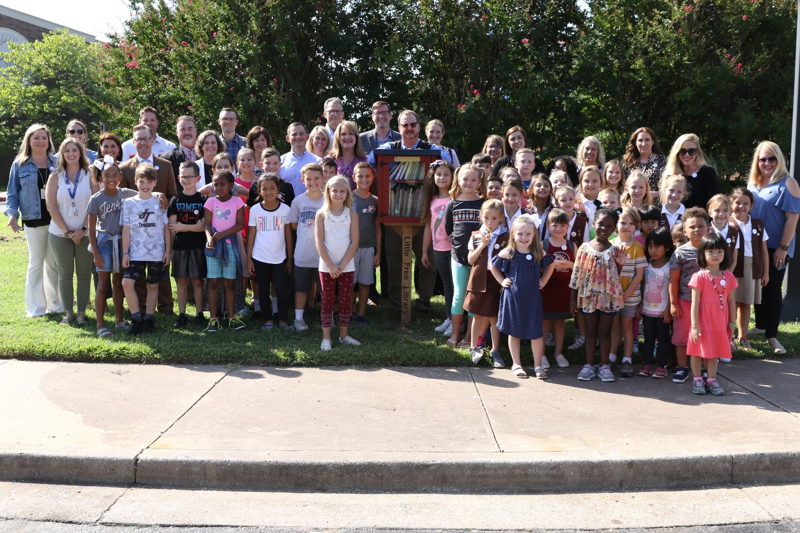 Todd Bol (center), Executive Director of Little Free Library, stands with students, staff members, and distinguished community guests, during the unveiling of the 75,00th Little Free Library on the campus of Jenks East Elementary.
