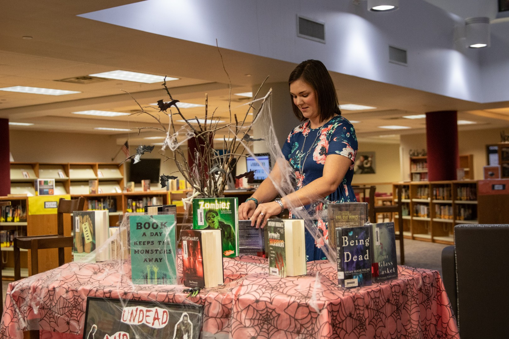 Emily Johnson arranges books on a new display inside the Media Center at Jenks Middle School.